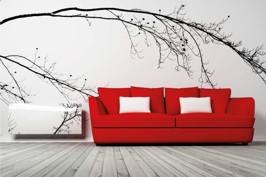 Red sofa on a wooden gray floor and a gray wall with wallpaper decor