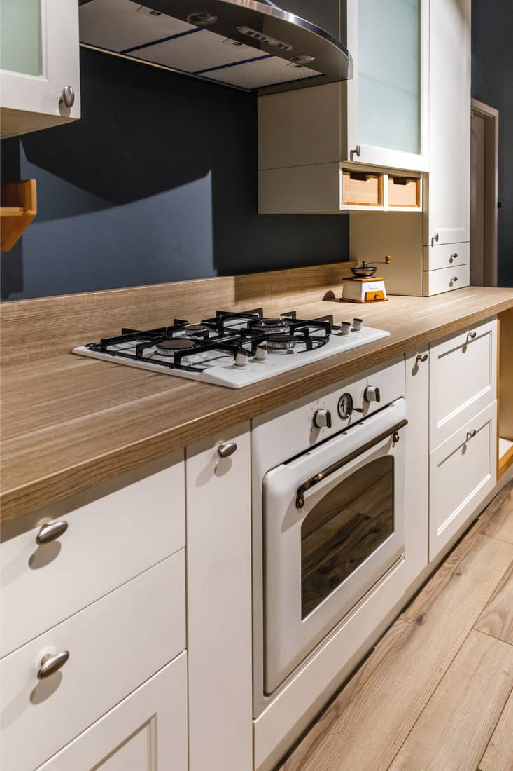 renovated kitchen interior with white cabinets and wooden butcher block countertop
