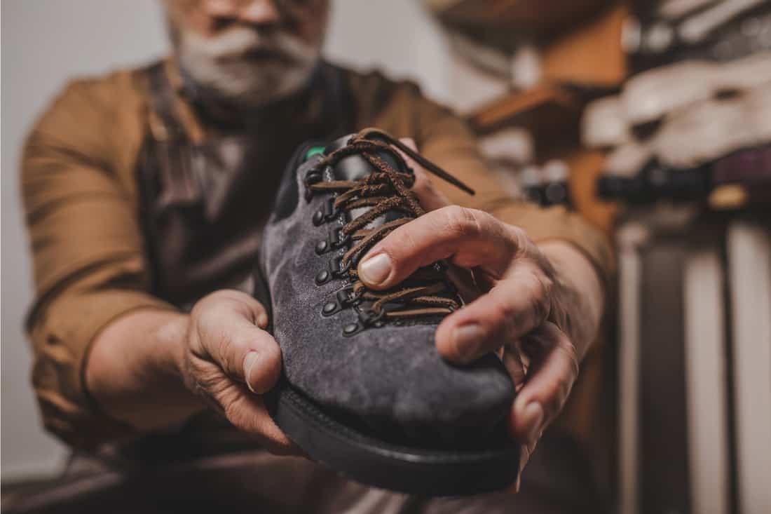 shoemaker holding suede shoe in workshop