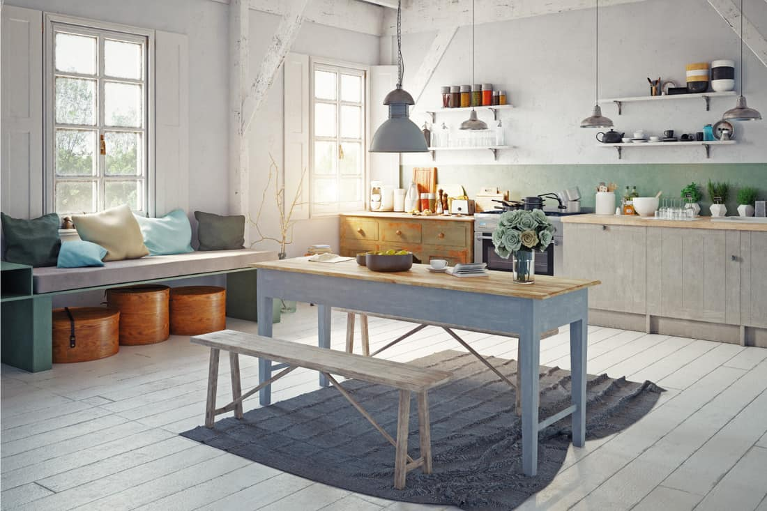 Vintage style kitchen interior with worn gray wood table and bench in the middle