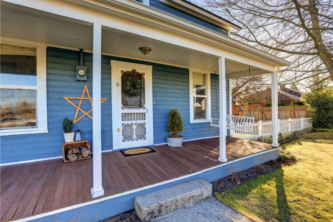 Wrap around front porch with rustic wooden decors on the walls