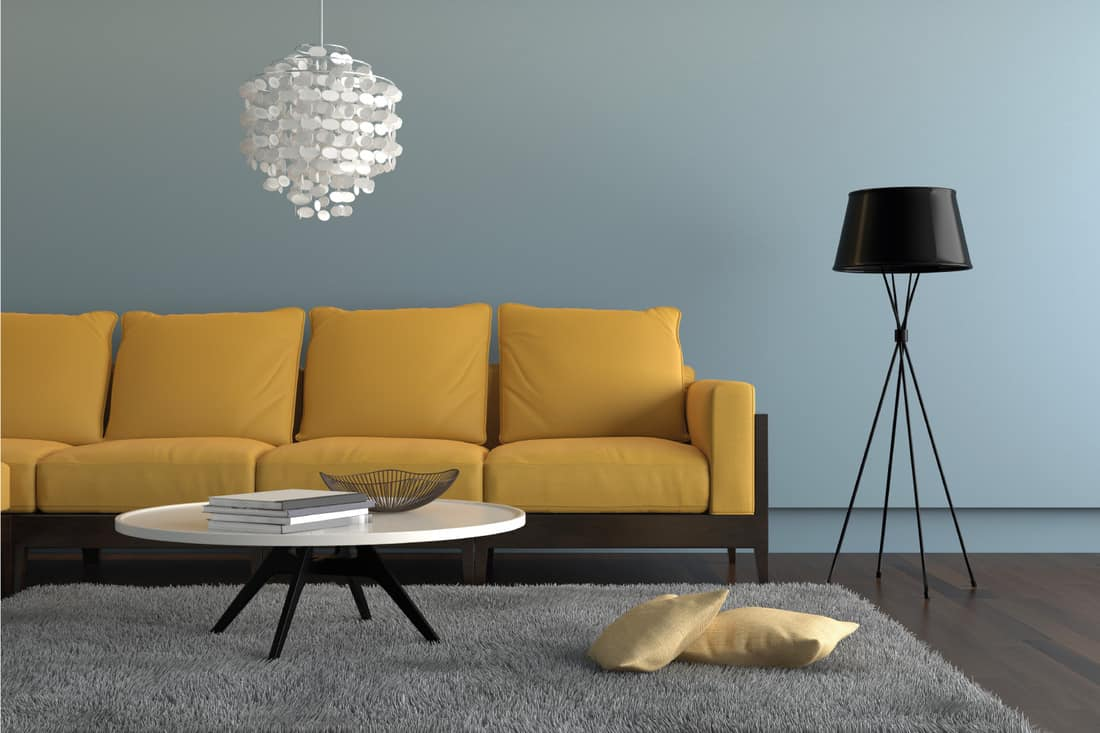 yellow orange sofa, with a lamp, ornate pendant and a table, gray carpet with two pillows, Light blue wall and dark wooden floor