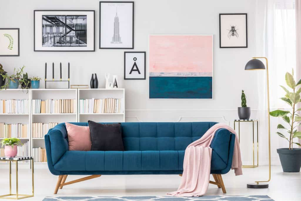 A Scandinavian themed living room with mock up picture frames, blue long sofa, and industrial made furnitures and table