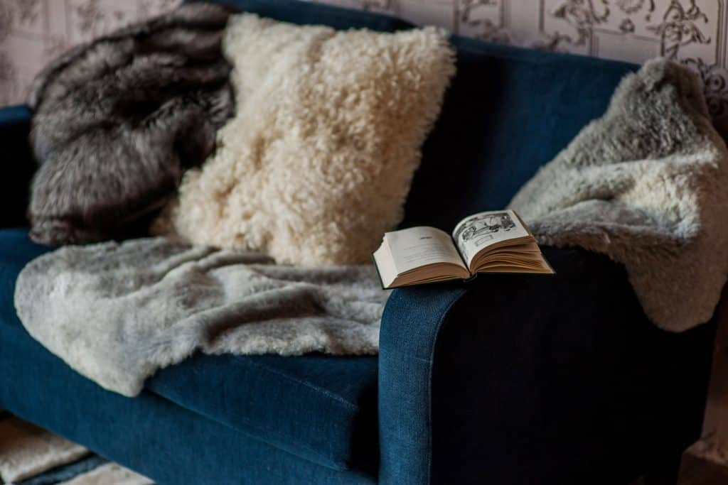 A blue loveseat with fur throw pillows on it and a book on the arm