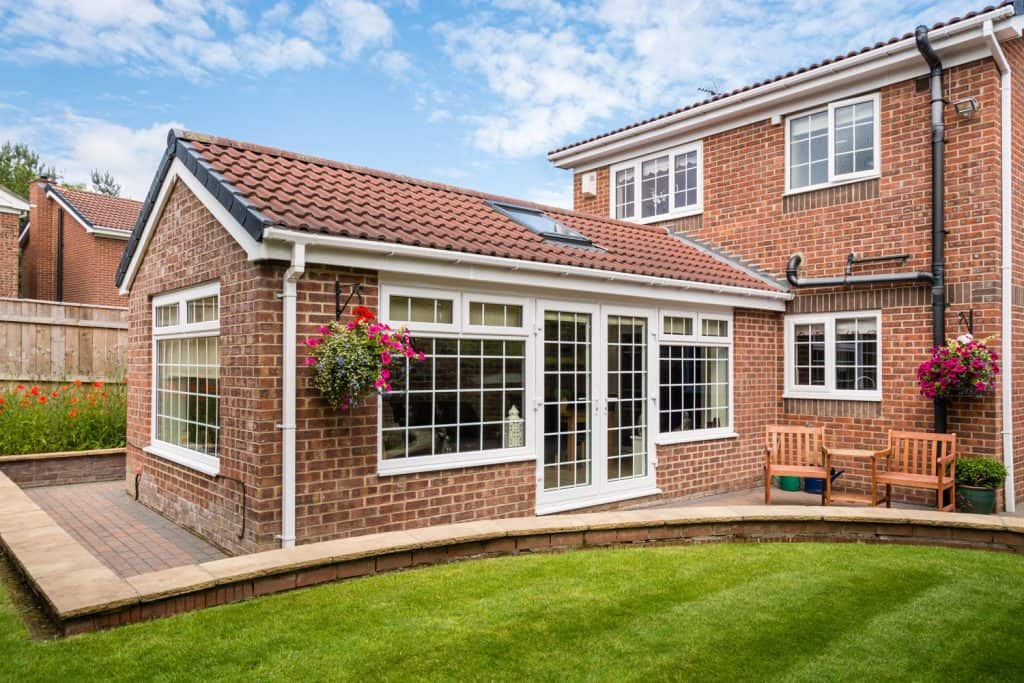 A brick home with a sunroom or conservatory room with a gorgeous grass lawn on the backyard