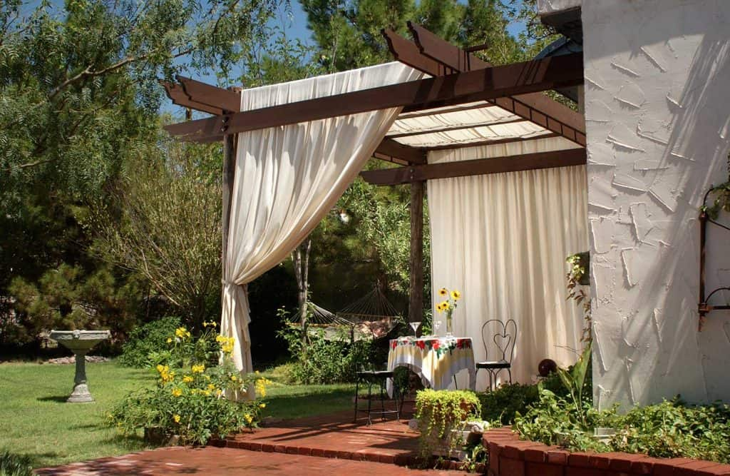 A brick patio with wooden patio posts and a cover of canvas curtains