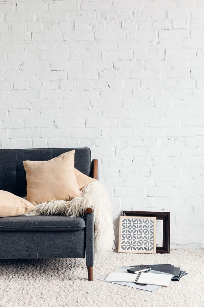 A bright living room with a white painted brick wall, dark gray colored sofa and notebooks laid on the floor