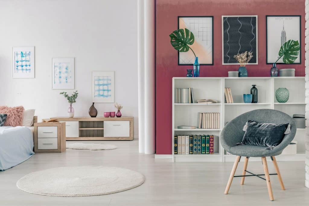 A burgundy colored accent wall, white walls on the background and a white colored bookshelf with indoor plants on top