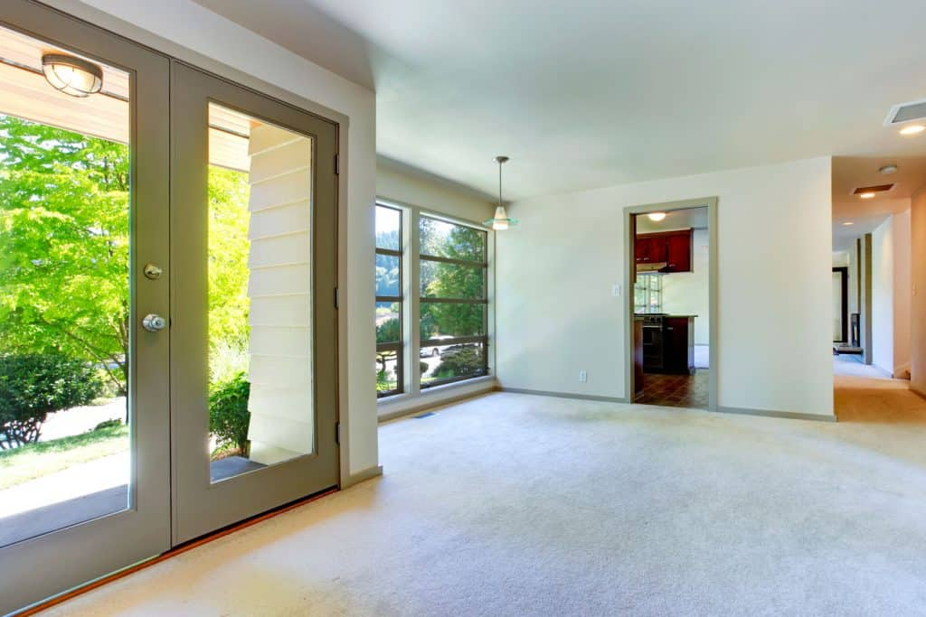 A carpeted living room with white colored walls, huge windows, and ceiling lights on every corner for proper lighting
