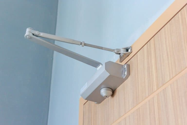 A closing mechanism of a wooden door with blue painted walls, How To Adjust A Screen Door Closer Mechanism