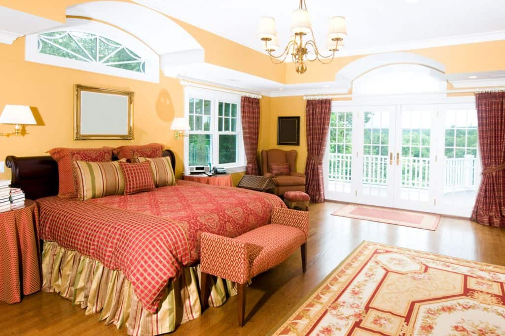 A country themed master bedroom with a huge comfortable bed, beige colored walls, and wooden flooring