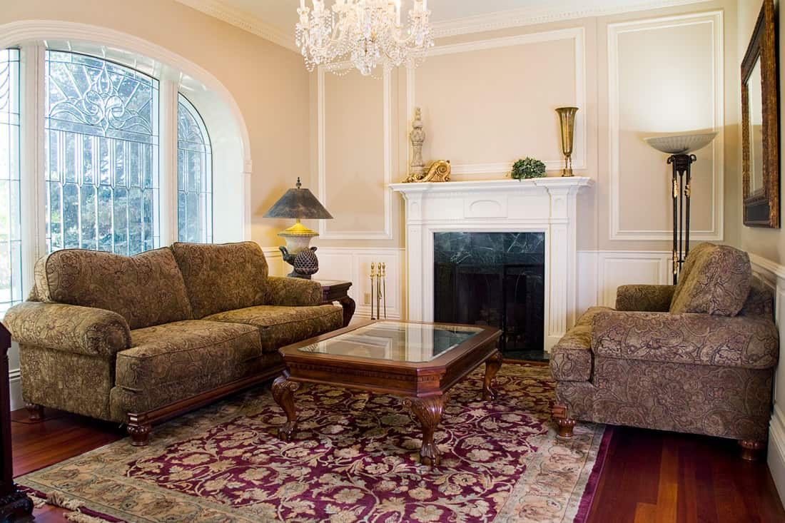A formal sitting/living room in a 19th century Victorian home with loveseat and sofa