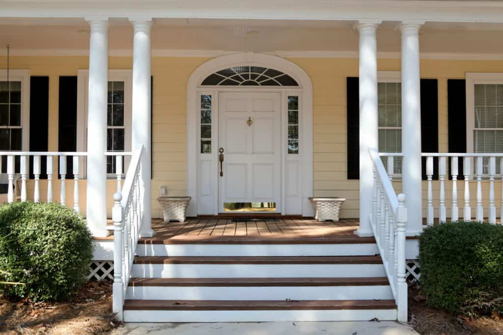 A front porch of a country home with white painted columns, white front door, with window panes