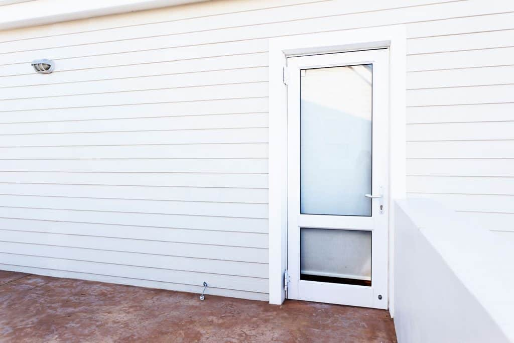 A glass screen door and wooden panel sidings painted in white