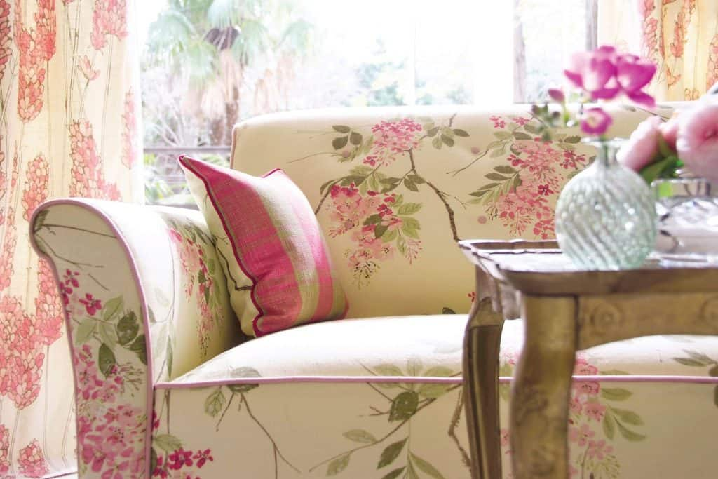 A gorgeous floral couch with a wooden coffee table in front with flowers and orchids