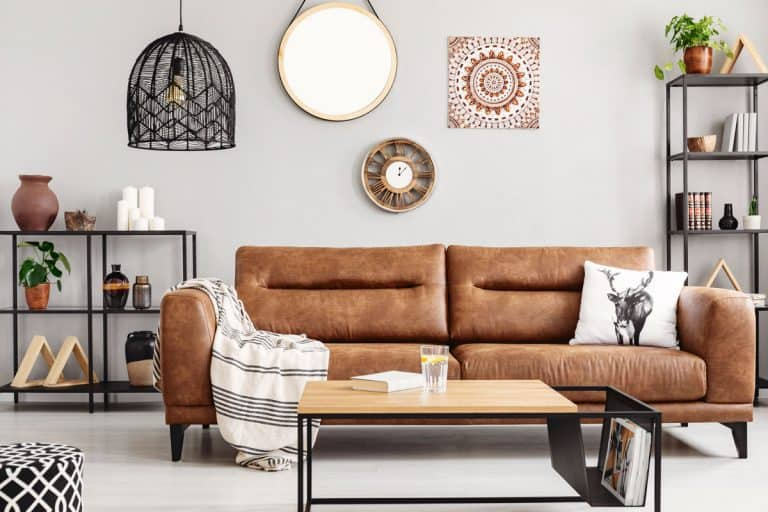 A gorgeous leather couch inside a white retro inspired living room with ethno styled cabinetry and dividers, How Long Does a Leather Couch Last?