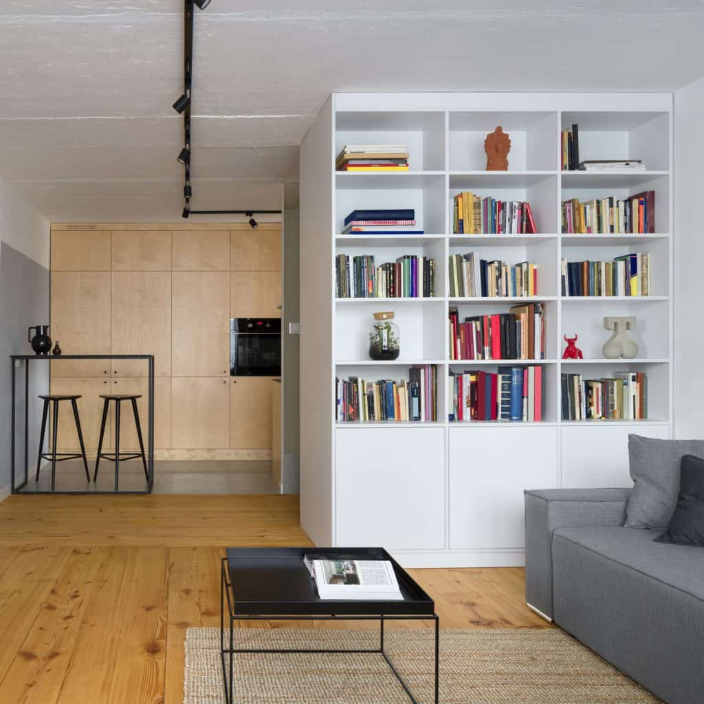 A gorgeous small apartment with wooden flooring, white colored bookshelf and a small table with a book on top