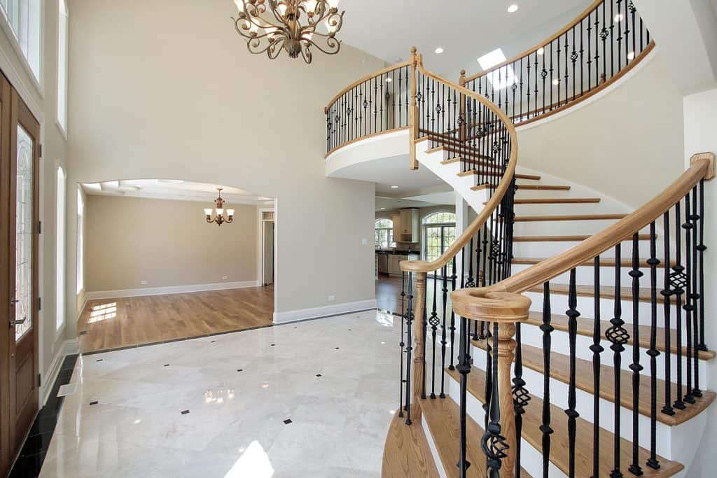 A grand foyer of a luxurious mansion with a winding staircase, white flooring, and a luxurious chandelier
