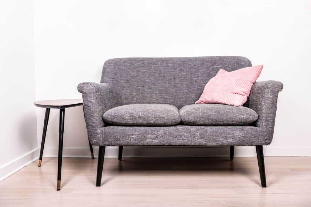 A gray love seat with a pink throw pillows on it