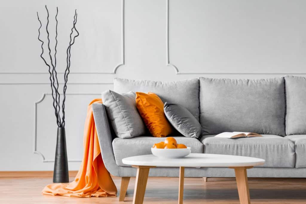 A gray loveseat with gray and orange throw pillows with a white coffee table in the front
