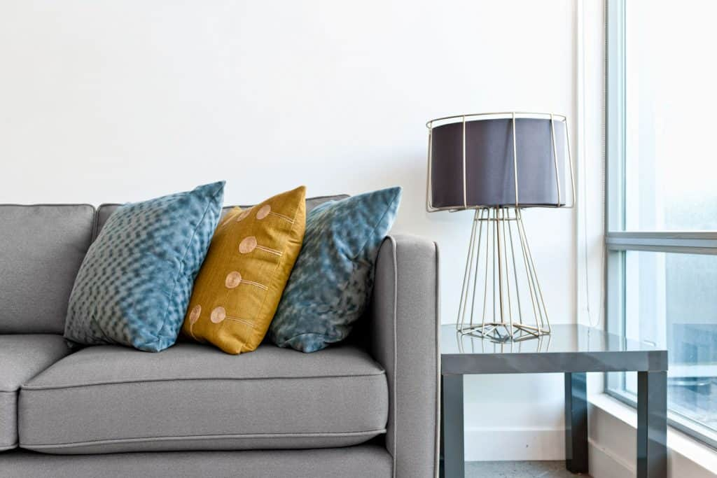 A gray sectional sofa with throw pillows placed next to a metal end table with a lamp on top