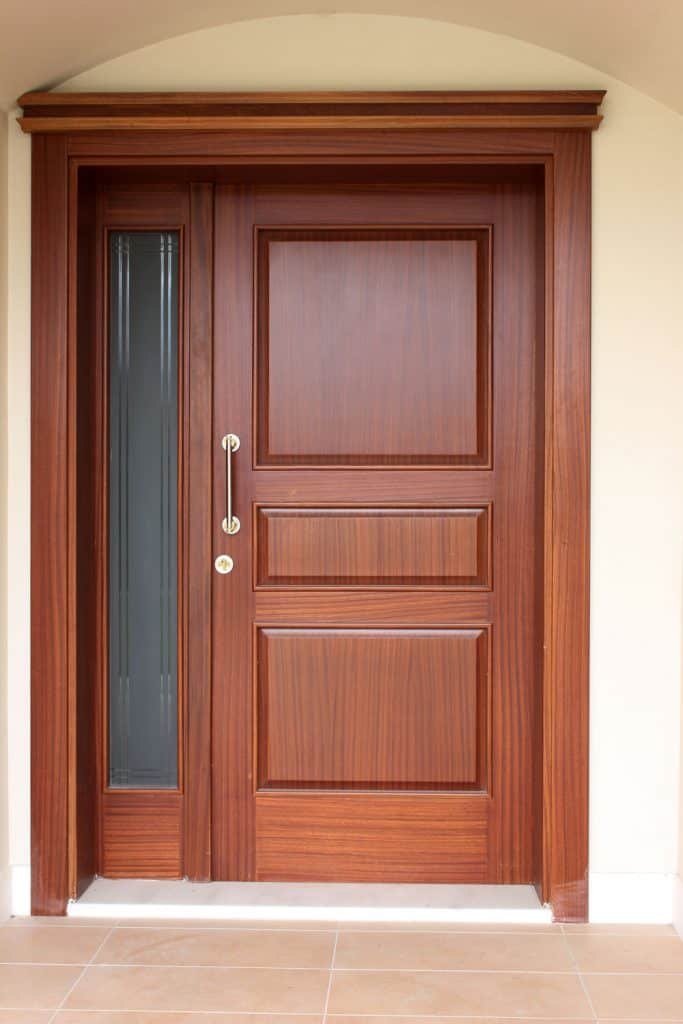 A hardwood front door with a small glass window on the side