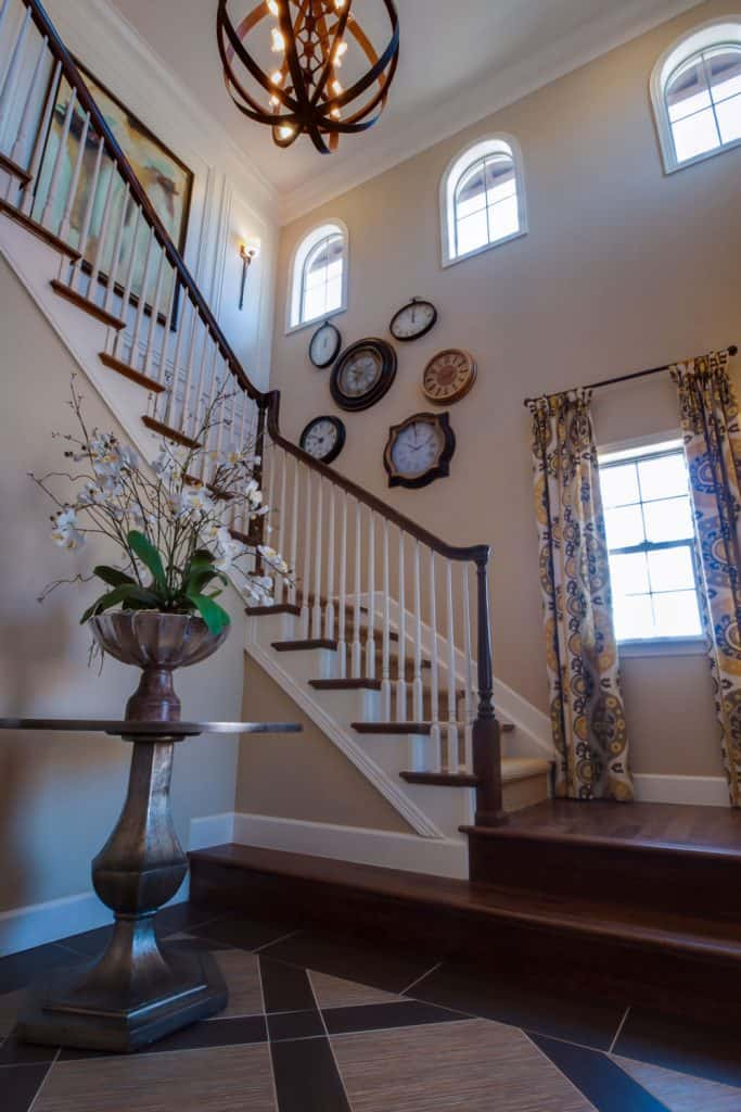A large staircase with dark wooden painted stair railing and white painted walls