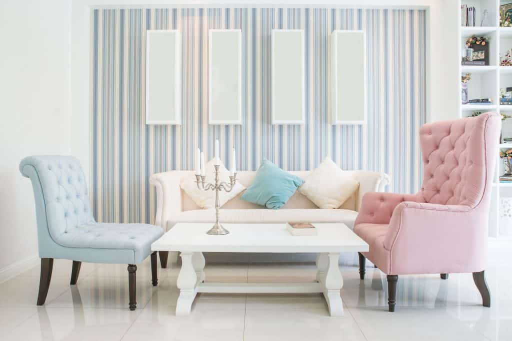 A light themed living room with bright pastel colored sofas, a white couch and a vintage designed coffee table