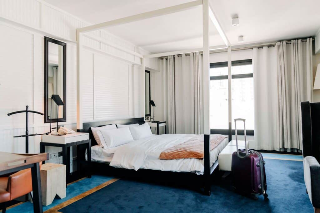 A luxurious bedroom with white painted walls, white beddings, blue carpet flooring, and a huge window with white curtains