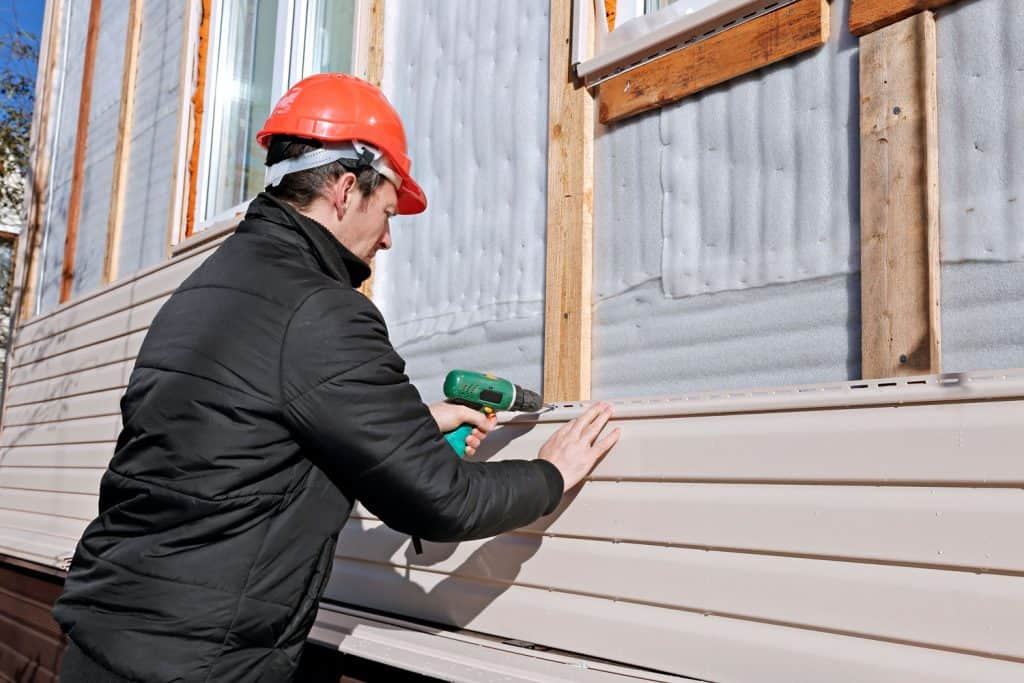 A man installing vinyl sidings on a mobile home