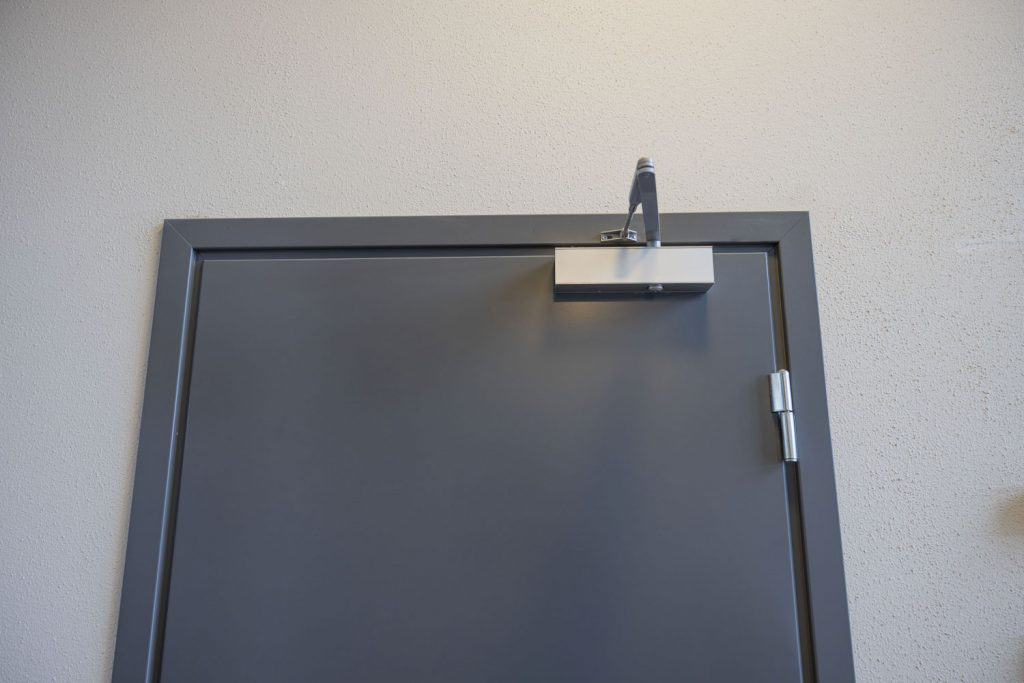 A metal door with a closing mechanism on the top