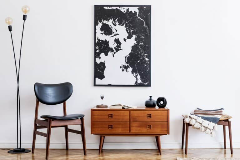 A minimalist concept living room with a small reading chair, wooden console table, and a mock up canvas with black and white painting, Where To Place A Console Table [7 Locations Explored]