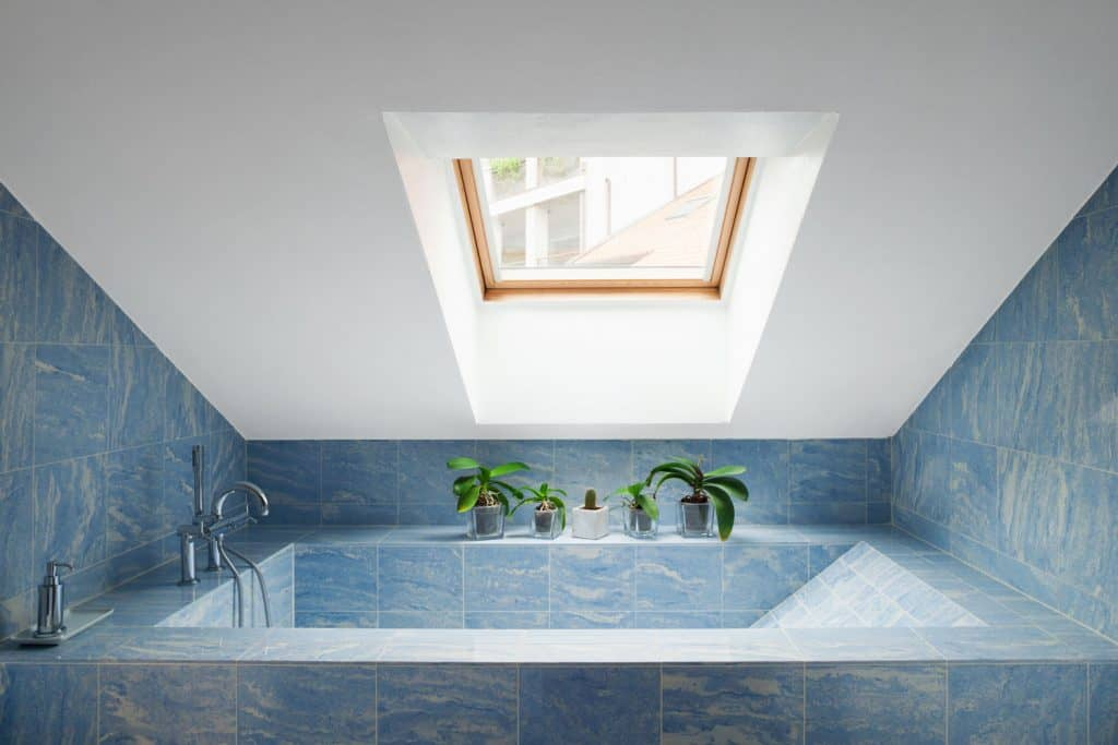 A modern attic with a blue tiled bathtub and white ceilings, and a sunroof