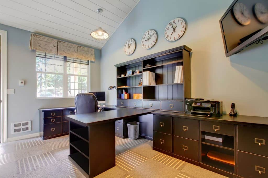 A modern home office with brown cabinet, three walls clocks, and a light blue painted wall