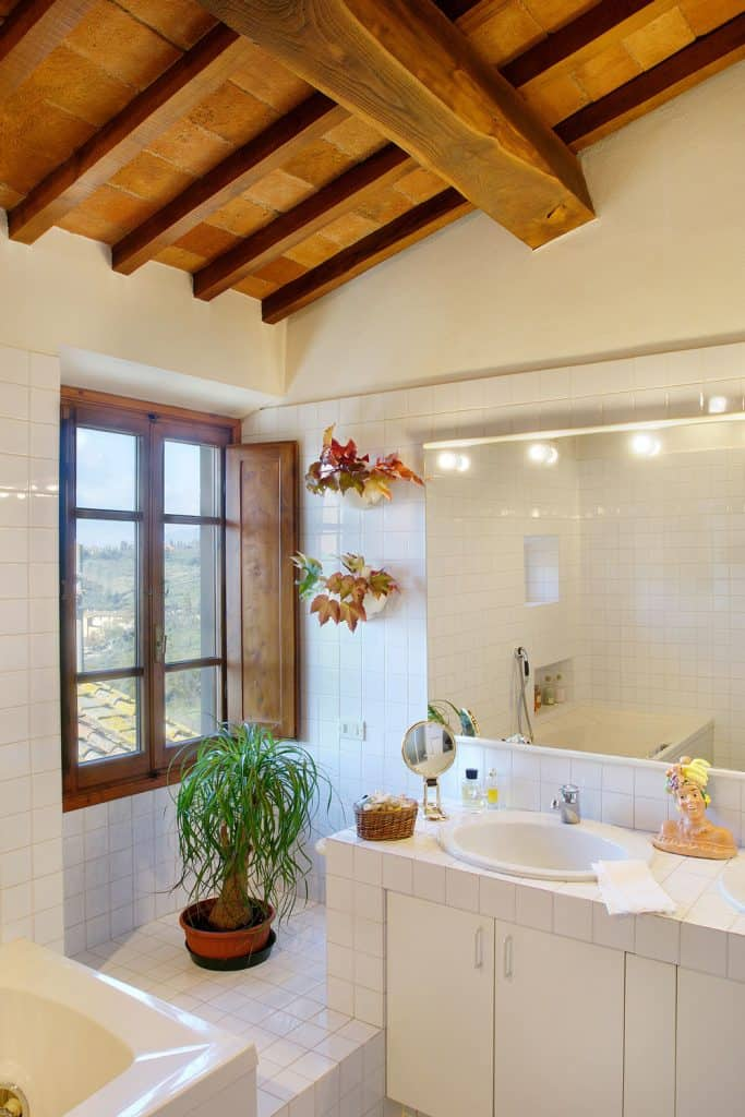A narrow rustic themed bathroom with white tiles, huge mirror, and a small window
