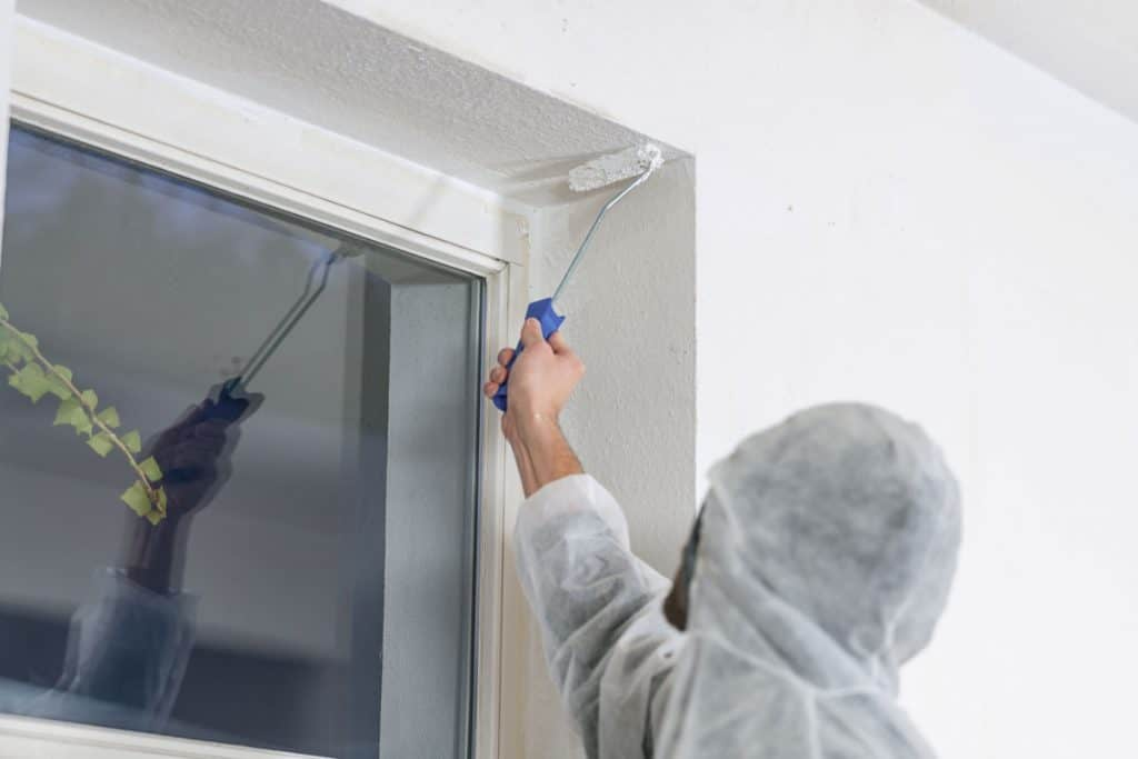 Painter using a roller paint to paint the corner of the window
