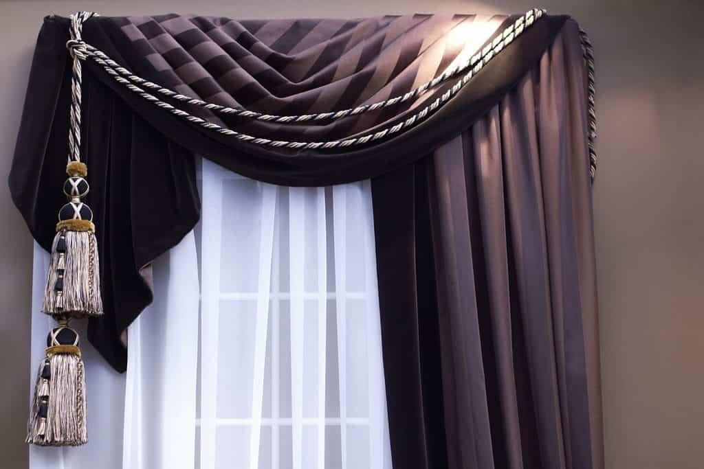A purple swag curtain inside a dark living room