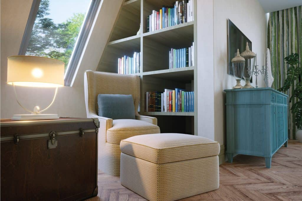 A reading area in attic bedroom includes a chair, a bookcase and books