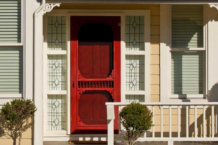 A red door with screen of a simple Victorian-style home with porch, Should the Screen Door Match Your Front Door?
