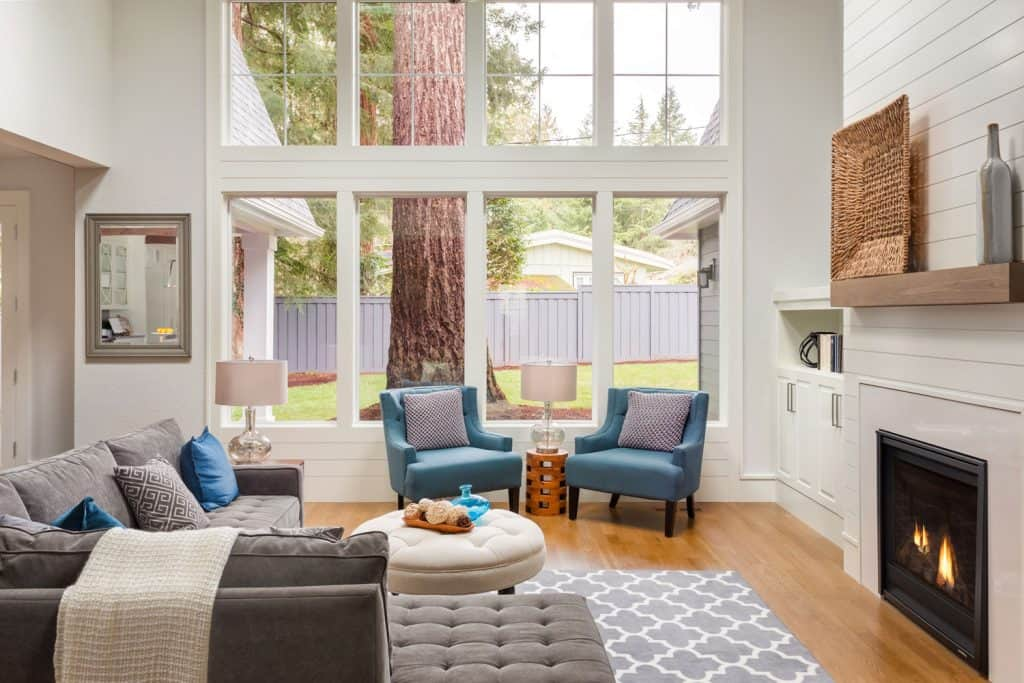 A retro inspired living room with gray and blue sofas, and end table with a lamp, and a fireplace on the side