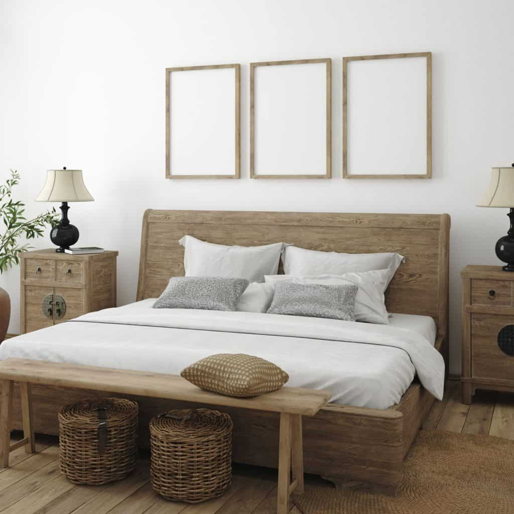 A rustic themed bedroom with wooden bed frame, wooden front chair, and three mock up picture frames on the wall