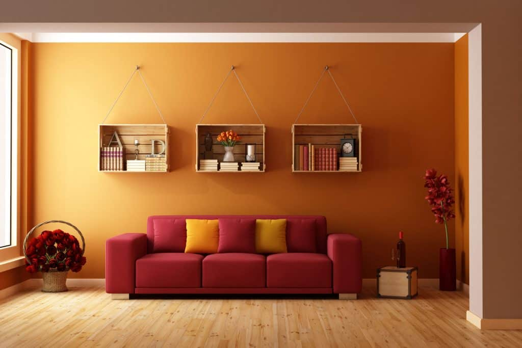 A rustic themed living room with three hanging cabinets, red sleeper sofa, orange painted walls, and wooden flooring