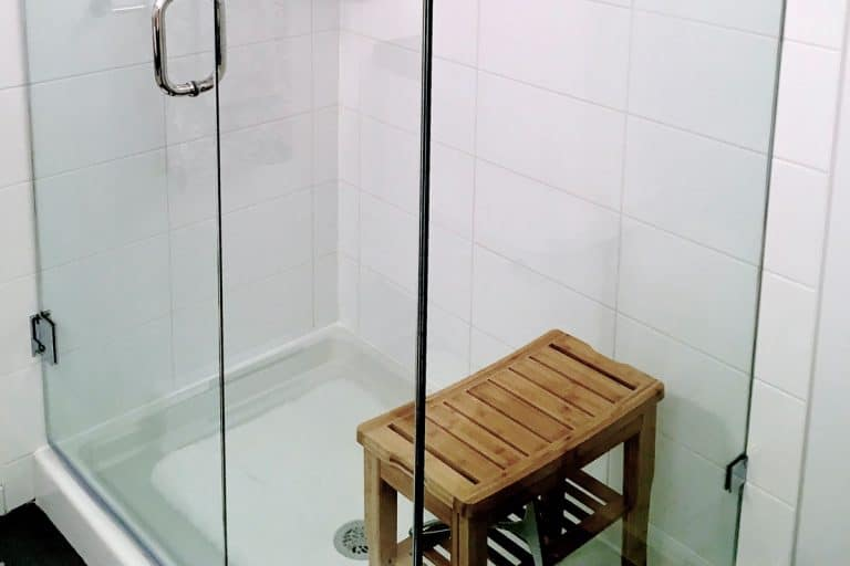 A small glass walled shower area with wooden shower bench, How Big Does A Shower Need To Be To Have A Bench?