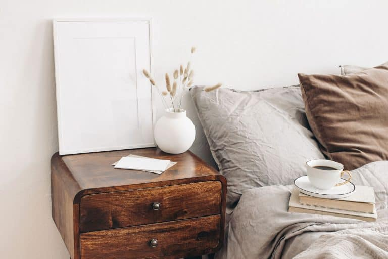 A small wooden nightstand placed next to a gray bed with gray and brown pillows, How Far Should Bedside Table Be From Bed?