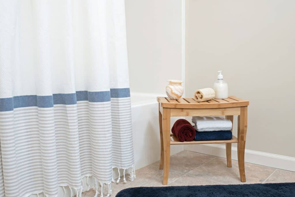 A small wooden shower bench with toiletries on the top and under placed next to a white shower curtain