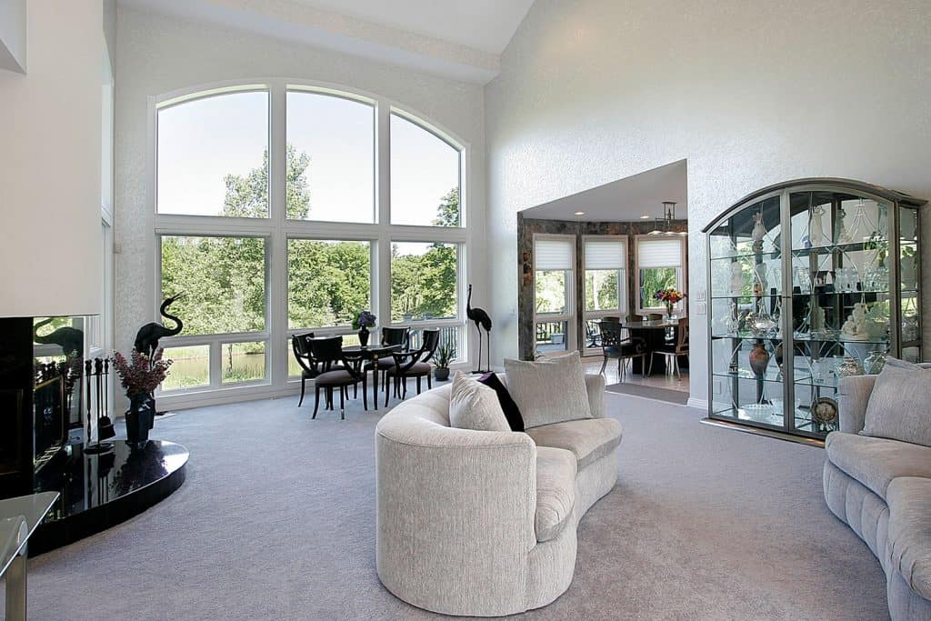 A spacious modern living room with carpeted flooring, huge arched window, and vintage designed sofas