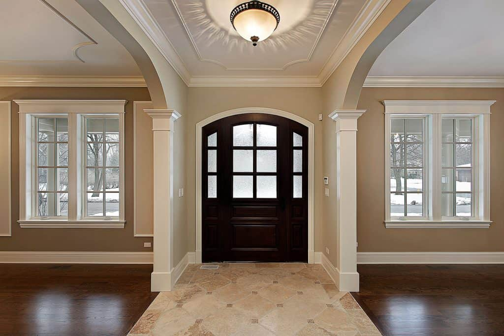 A Mediterranean themed foyer of a house with black hardwood French door and white painted window casing
