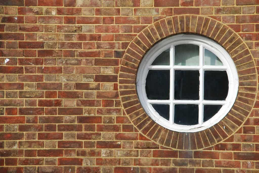 A vintage round window with white painted casement made with bricks