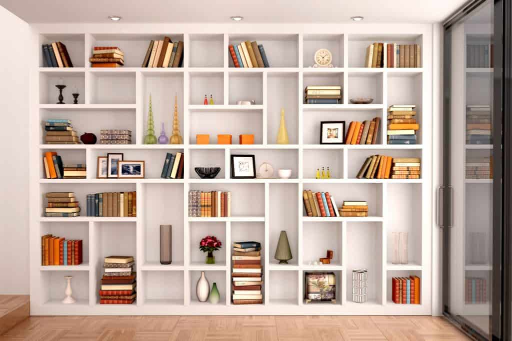A white colored bookcase with books, picture frames, and other furnitures inside