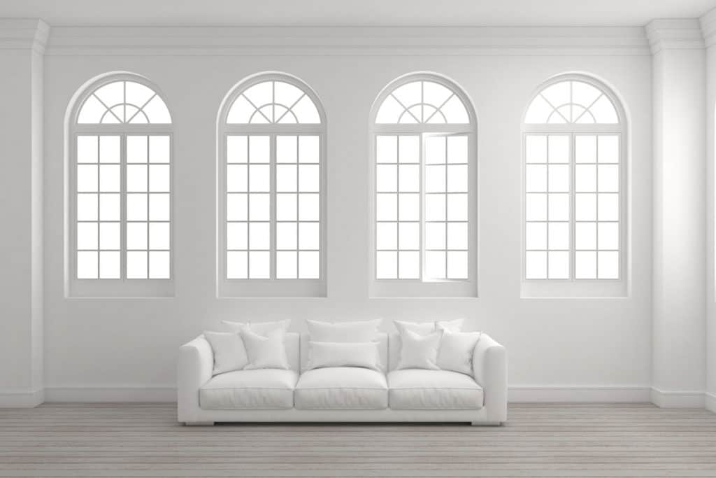 A white living room with a white sofa and four arched windows